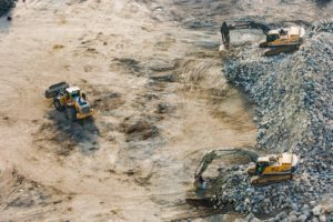 Earth movers digging rocks in quarry